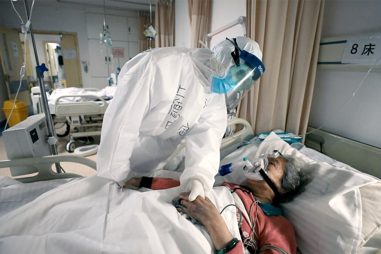 A health care worker in PPE stands over a patient in a hospital bed.