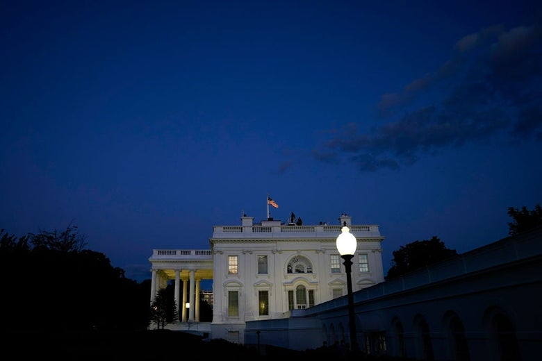 The White House is seen from the side against a darkening sky.