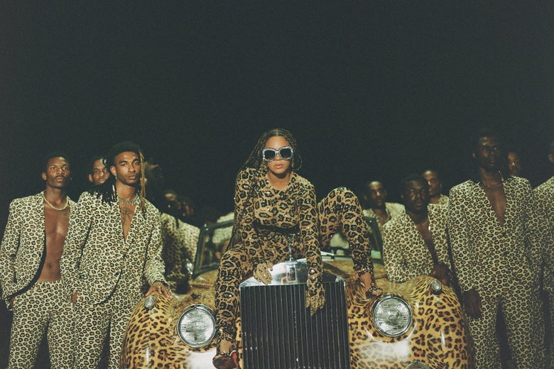 Beyoncé sits atop the grill of a vintage-looking, leopard-print automobile, surrounded by Black men wearing leopard-print blazers and leopard-print pants. She wears sunglasses, braids, and leopard print.