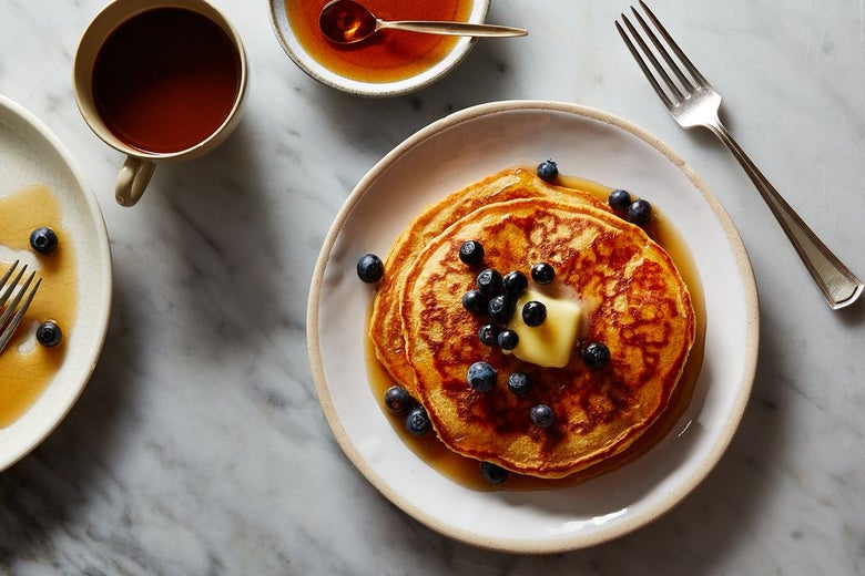 Stack of pancakes topped with blueberries, a pat of butter, and syrup, next to a fork, a cup of coffee, a small dish of syrup, and a finished plate of pancakes on a marble surface