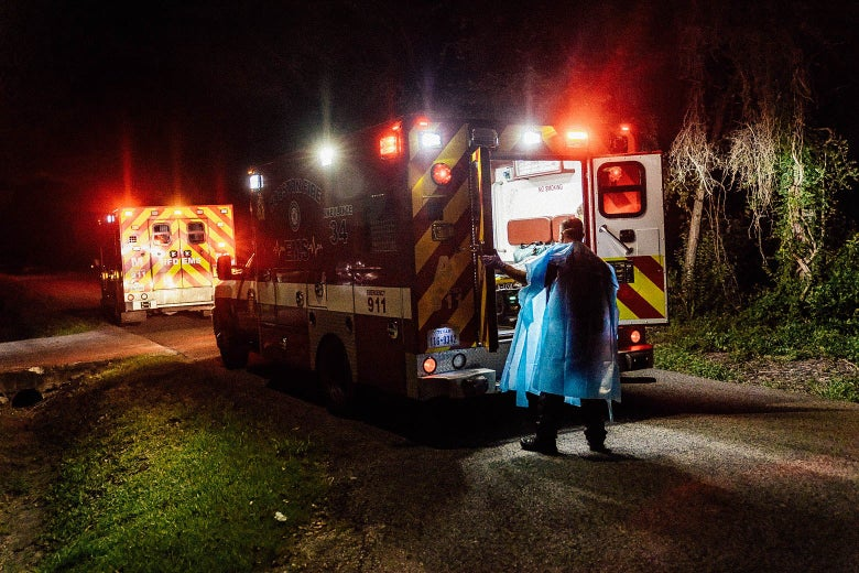 A person in PPE opens the back doors to an ambulance in the dark.