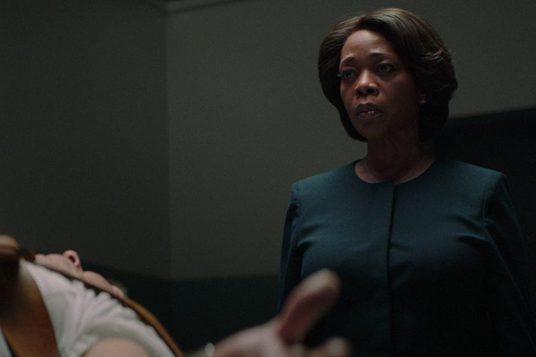 Alfre Woodard in a blue suit stands over a prone, bound man.