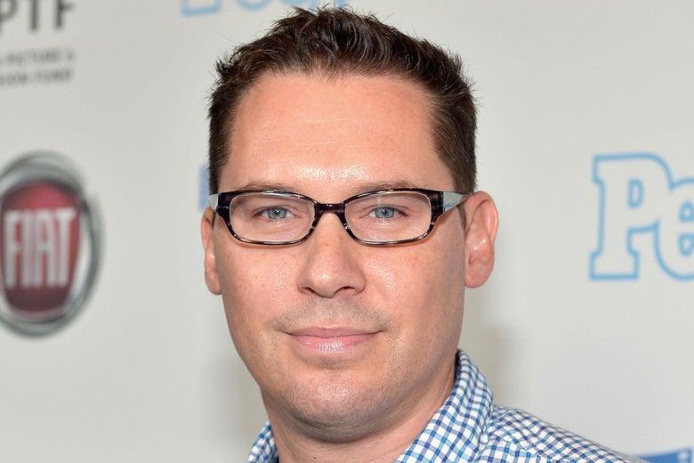 Bryan Singer, in black-rimmed glasses, smiles slightly.
