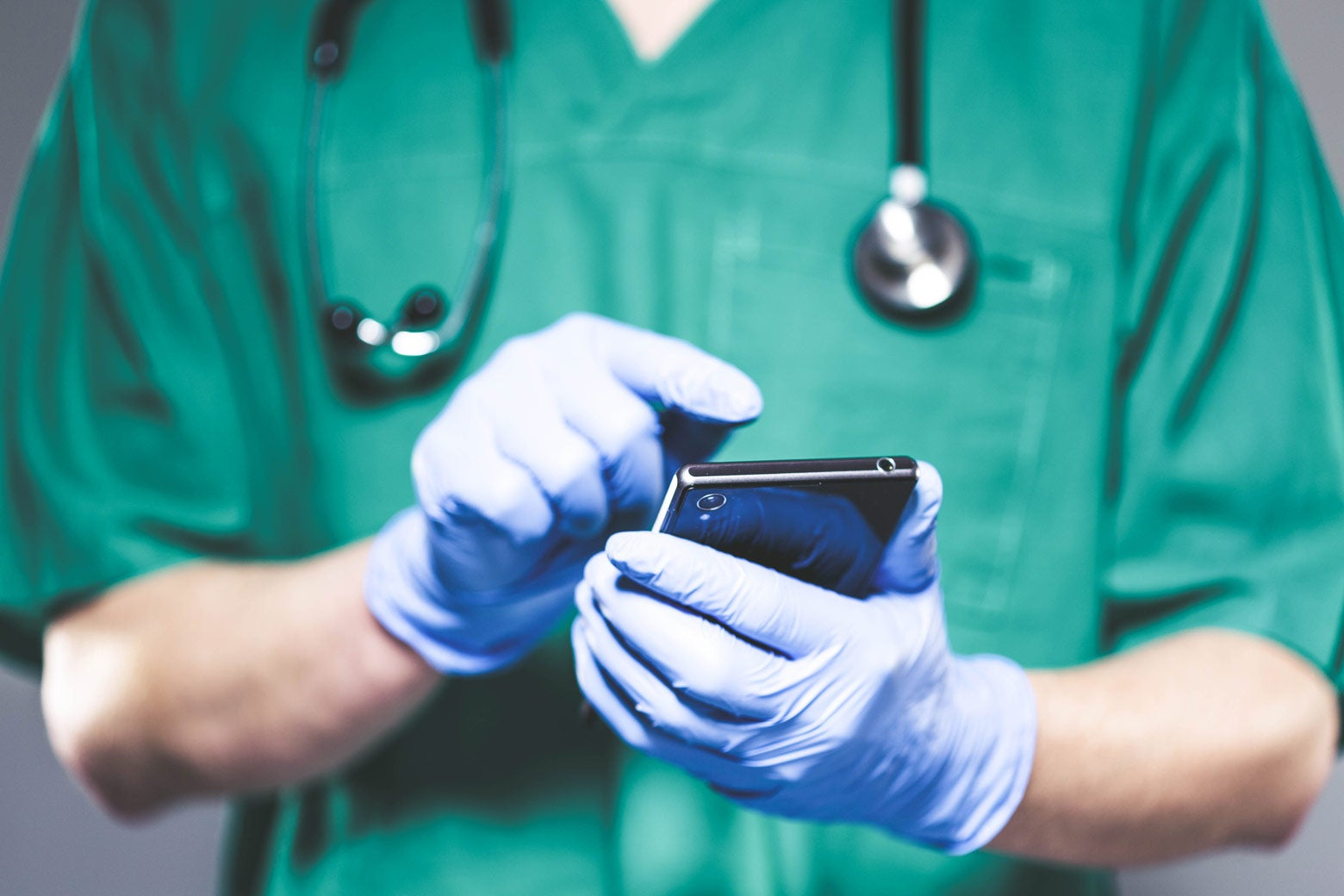 A doctor in scrubs, wearing gloves, looking at a cellphone.