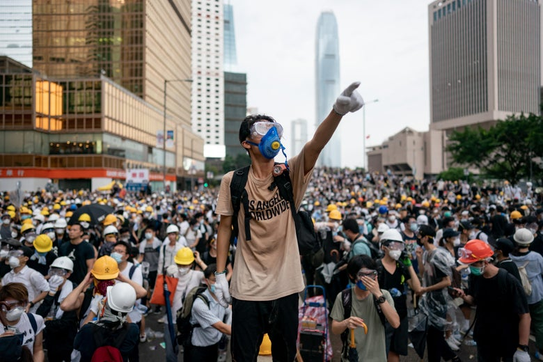 A protester in a gas mask stands in front of large crowds in Hong Kong.