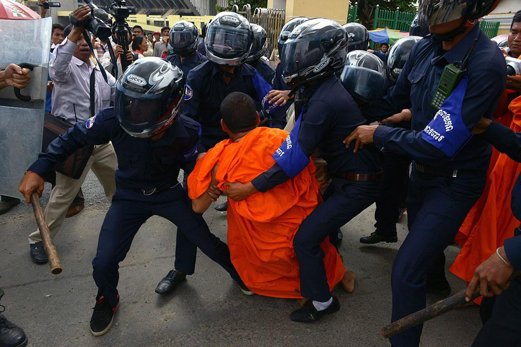 Cambodian security guards arrest an activist Buddhist monk during a protest in front of Phnom Penh municipal court on November 11, 2014.