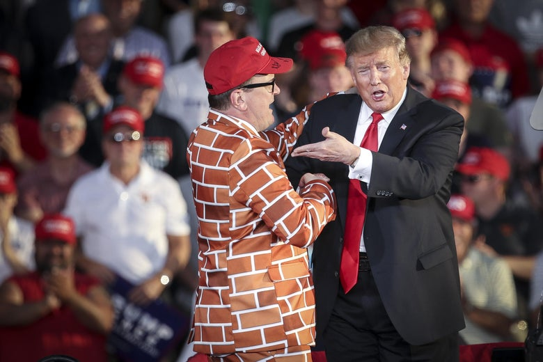 President Trump calls up a mean wearing a jacket with bricks representing a border wall to the stage during a 'Make America Great Again' campaign rally at Williamsport Regional Airport, May 20, 2019 in Montoursville, Pennsylvania.