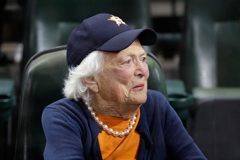 Barbara Bush, wearing a T-shirt, pearls, and a Houston Astros baseball cap, is seen sitting in stadium seating.