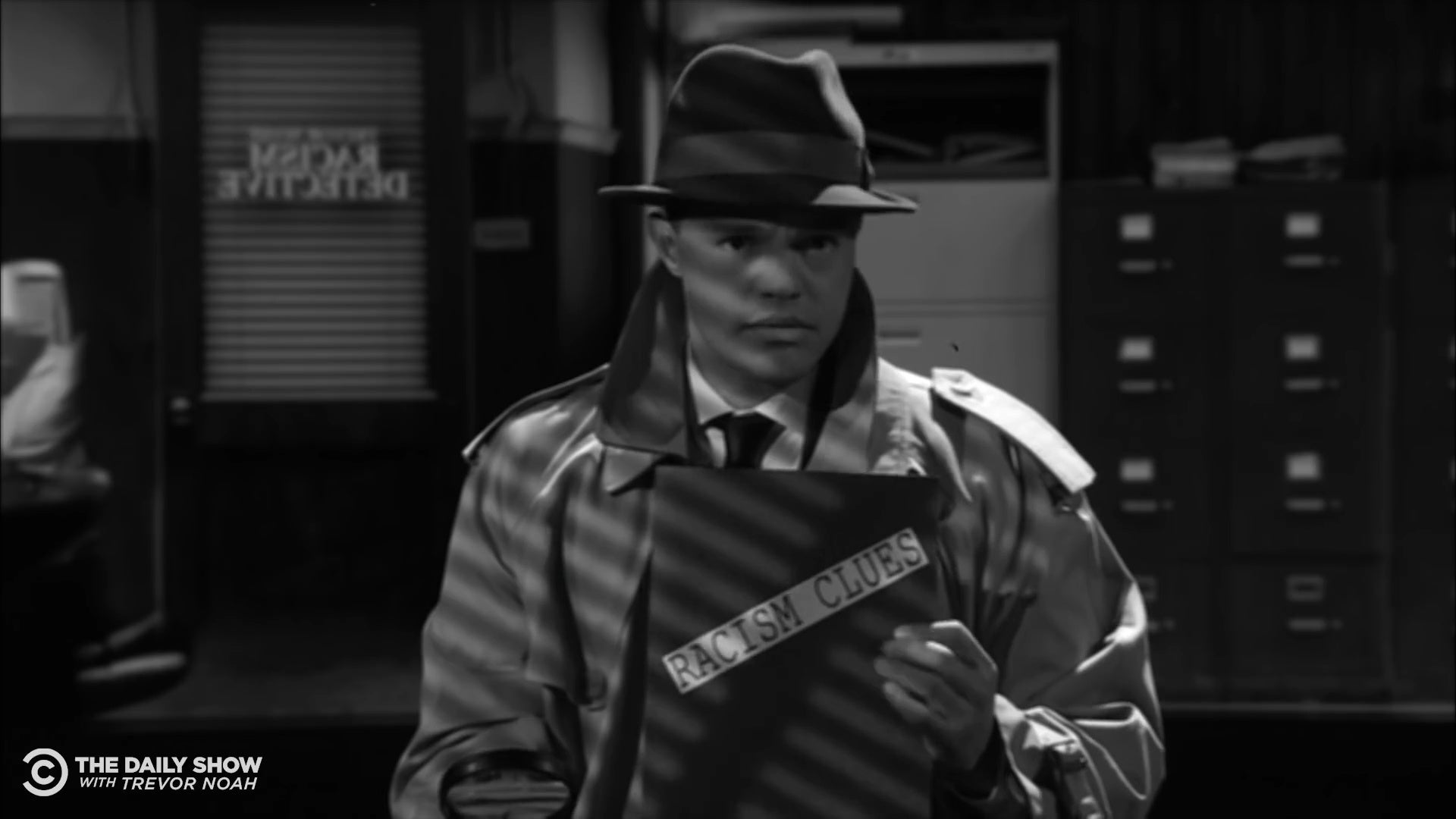 """Trevor Noah dressed as a 1940s detective, holding a folder labeled """"racism clues."""""""