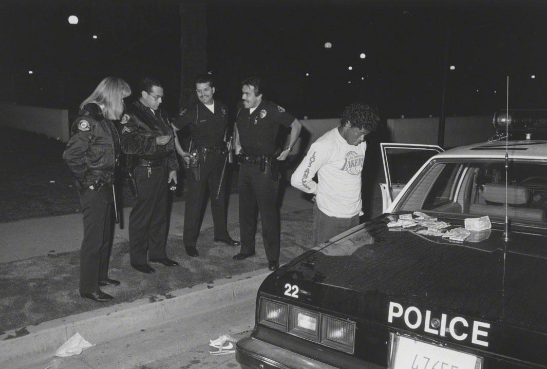 66/7/86 Agent Olquin holding rock cocaine piece found in drug sales suspect's folded money. Sunset Avenue.