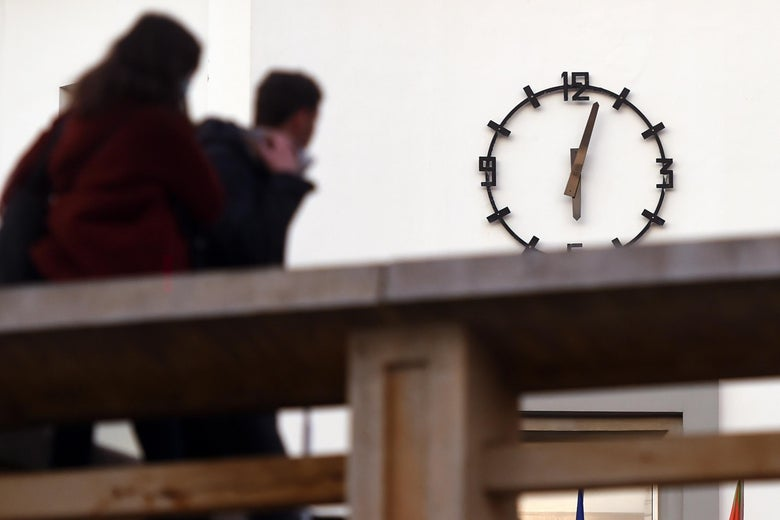 Two people look at a clock on a wall.