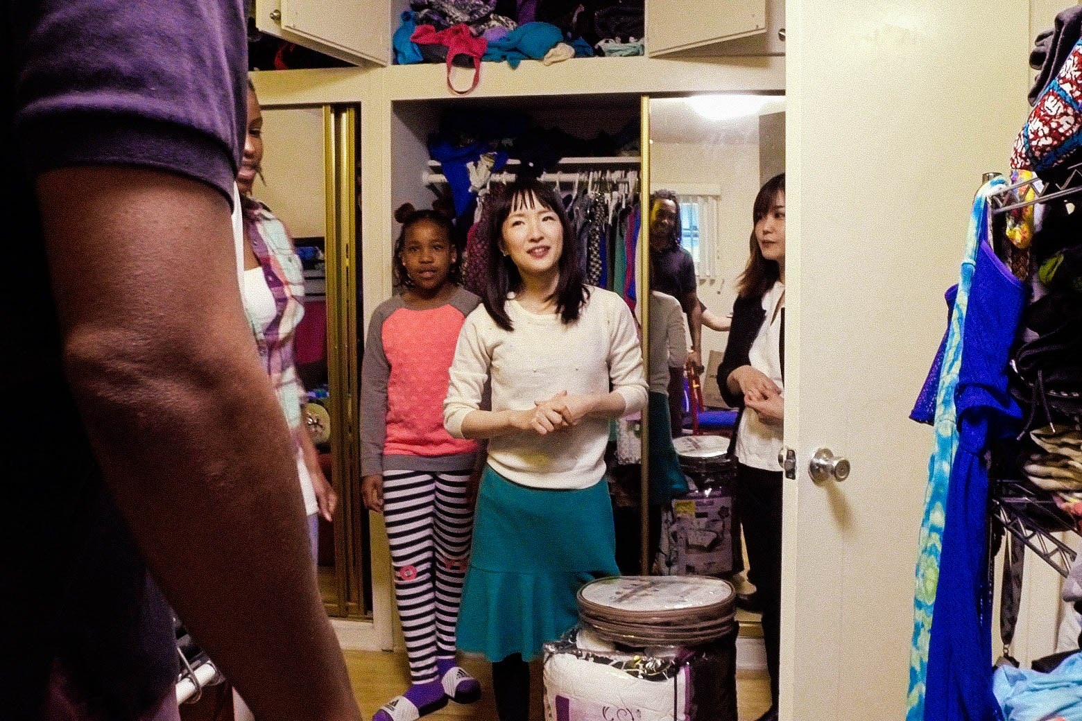 KayCi Mersier and Marie Kondo next to a closet, rack, and cabinet full of clothes.