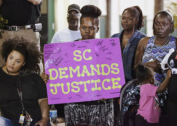 A protester holds a sign during a late rally at city hall in Nor,A protester holds a sign during a late rally at city hall in North Charleston, South Carolina April 8, 2015.