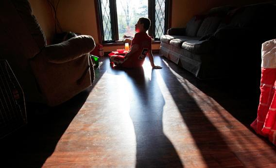 Parker Roos, who suffers from a form of autism called Fragile X, sits in the sun as he watches cartoons at his home in Canton, Ill., April 4, 2012.