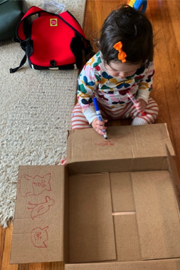 A child drawing on an Amazon box.