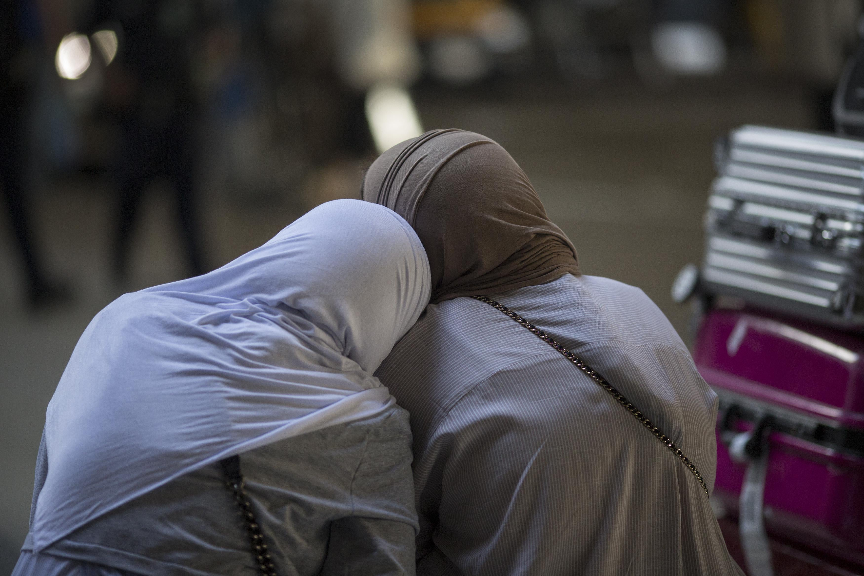 Two Muslim women lean against each other, as seen from behind. Suitcases can be seen next to them.