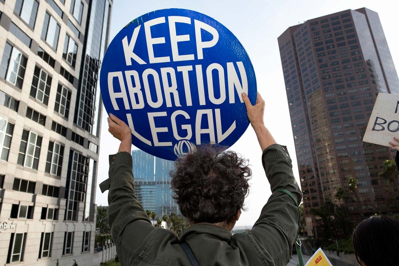 "A protester holds up a sign reading ""KEEP ABORTION LEGAL."""
