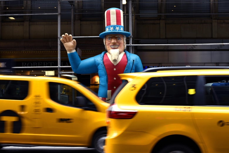 New York City cabs pass by a  balloon of 'Uncle Sam' in front of a building on Madison Avenue in New York March 1, 2018.