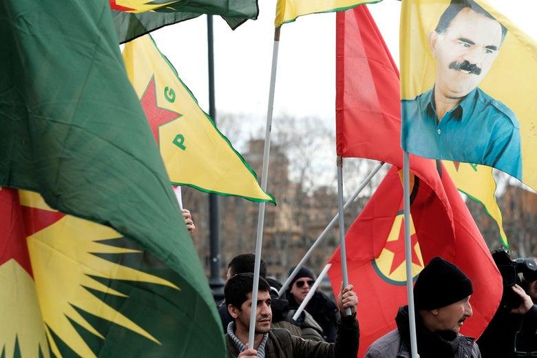 Demonstrators wave red and yellow Kurdish flags alongside a portrait of Abdullah Öcalan.