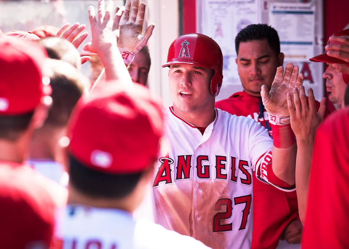 Los Angeles Angels of Anaheim Center field Mike Trout greeted by his teammates after being lifted for a pinch running after he drove in a run for his 100th RBI of the season during the game against the Houston Astros played at Angel Stadium of Anaheim in Anaheim, CA.