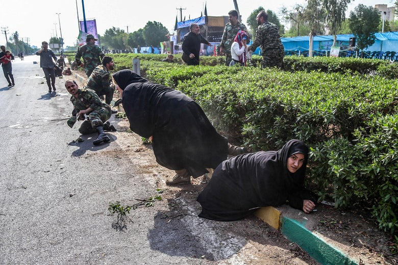 This picture taken on September 22, 2018 in the southwestern Iranian city of Ahvaz shows Iranian women and soldiers taking cover next to bushes at the scene of an attack on a military parade.