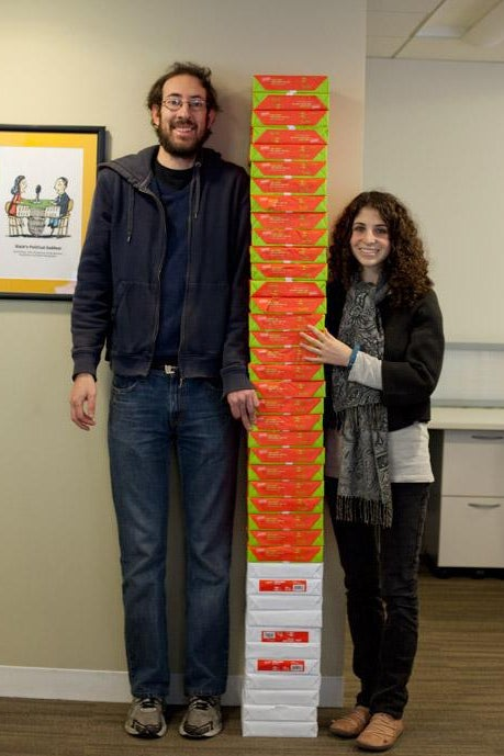 Two people standing by paper.