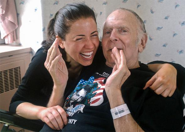 Author Lili Anolik and Al Goldstein at his nursing home last year. Lili laughs as Al holds out his hands to give a rough estimate of his penis size.