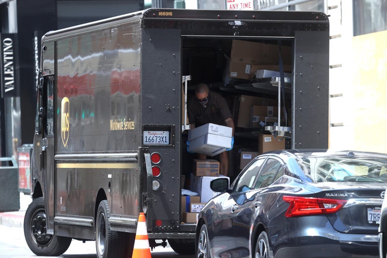 A UPS driver stands inside his truck unloading packages.