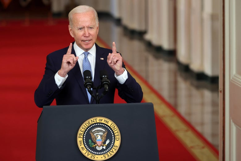 Biden standing behind a mic, pointing up