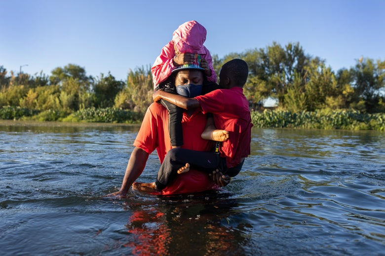 Two small children wrapped around their father's back and torso as he wades through a river