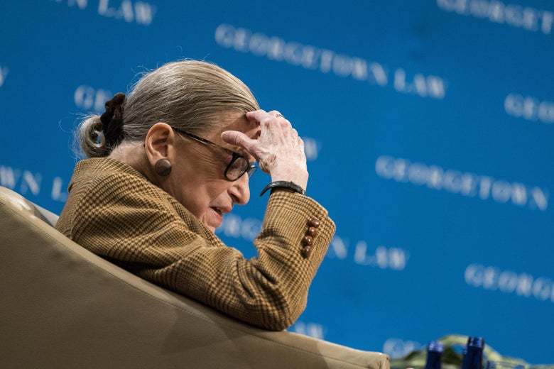 Ruth Bader Ginsburg sits in a chair and puts her hand to her head.