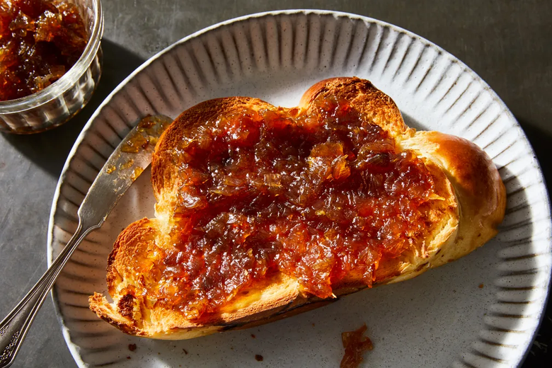 Toast topped with shallot jam next to a butter knife on a plate, with a small glass jar of more shallot jam next to the plate