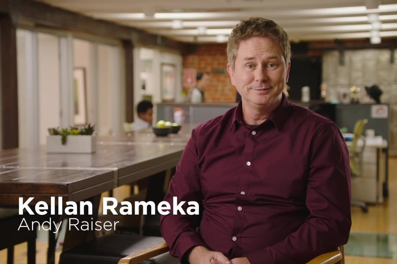 """A man in a dark red shirt sits in an industrial office space, looking politely at the camera. A chyron reads """"Kellan Rameka: Andy Raiser."""""""