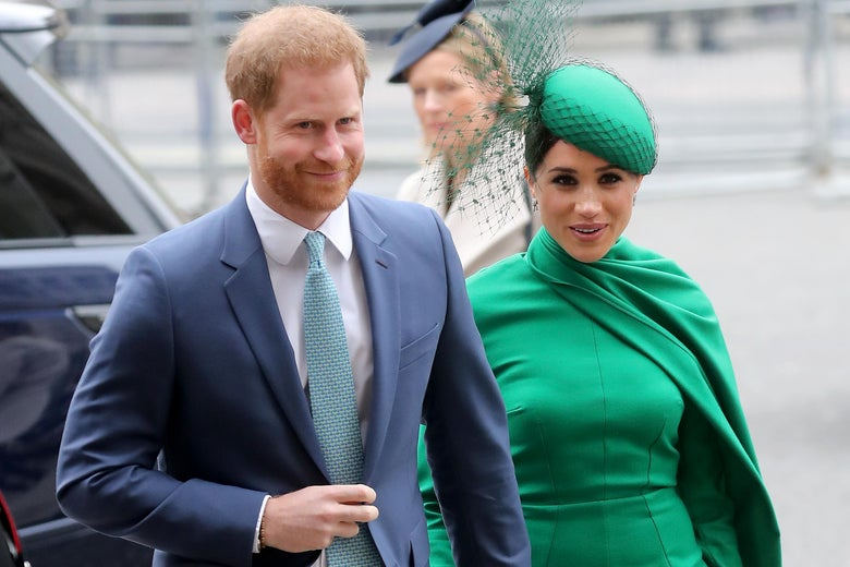 Prince Harry wearing a suit standing next to Meghan Markle in a green outfit with cape and green hat, seen from the waist up, in London.
