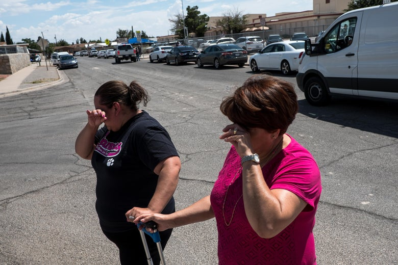 Erica and Alma Rios cry on the street outside the school.