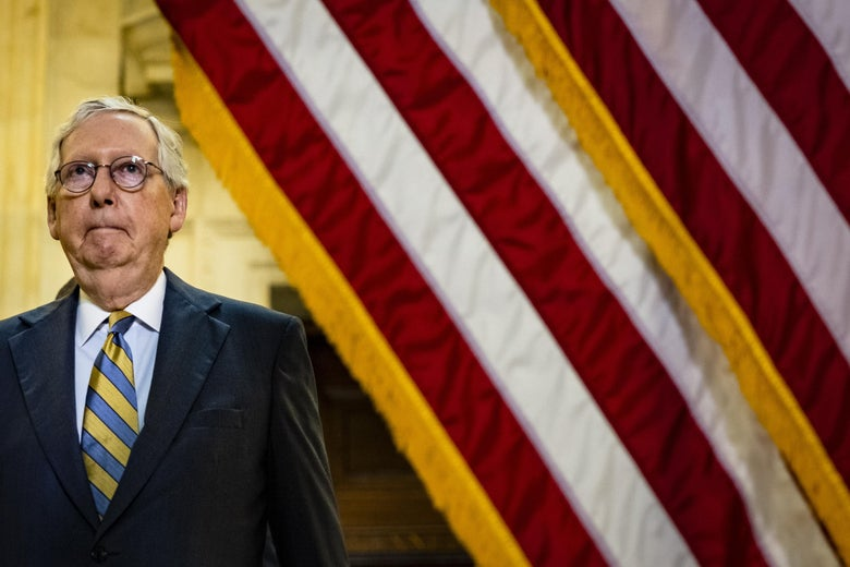 McConnell standing next to a flag