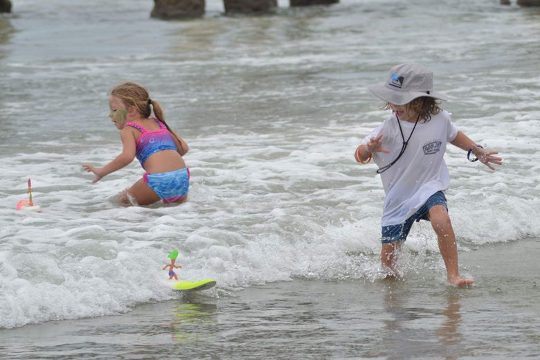 Children playing with Surfer Dudes in the waves.