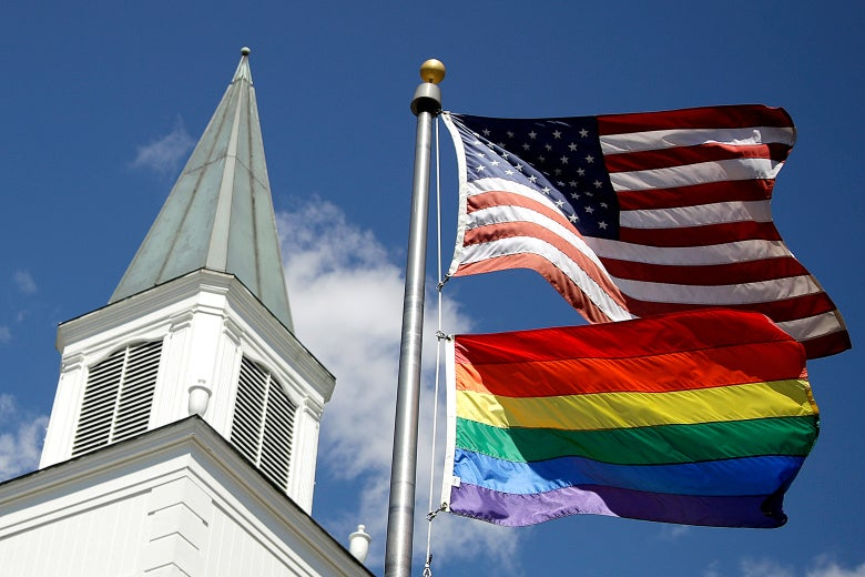 A rainbow flag flies along with the U.S. flag in front of a Methodist church.