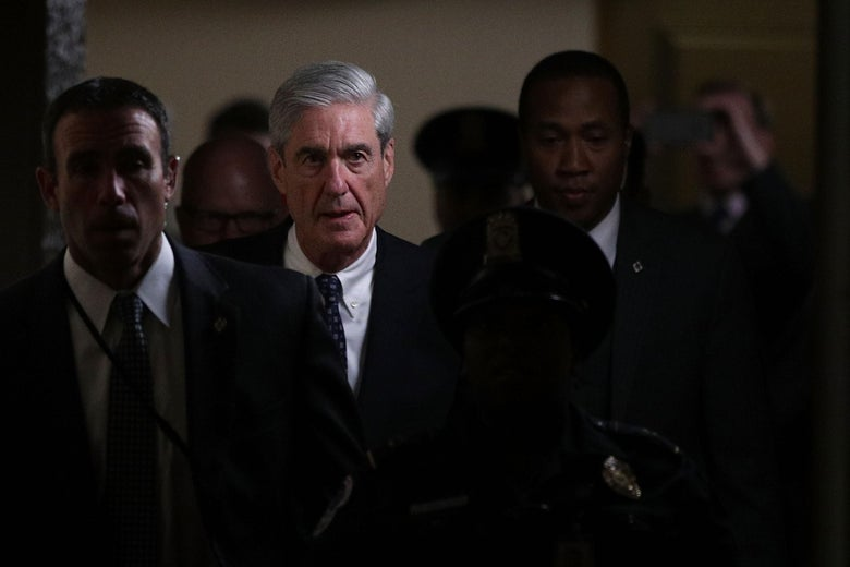 Special counsel Robert Mueller walks down a hallway, surrounded by staffers.