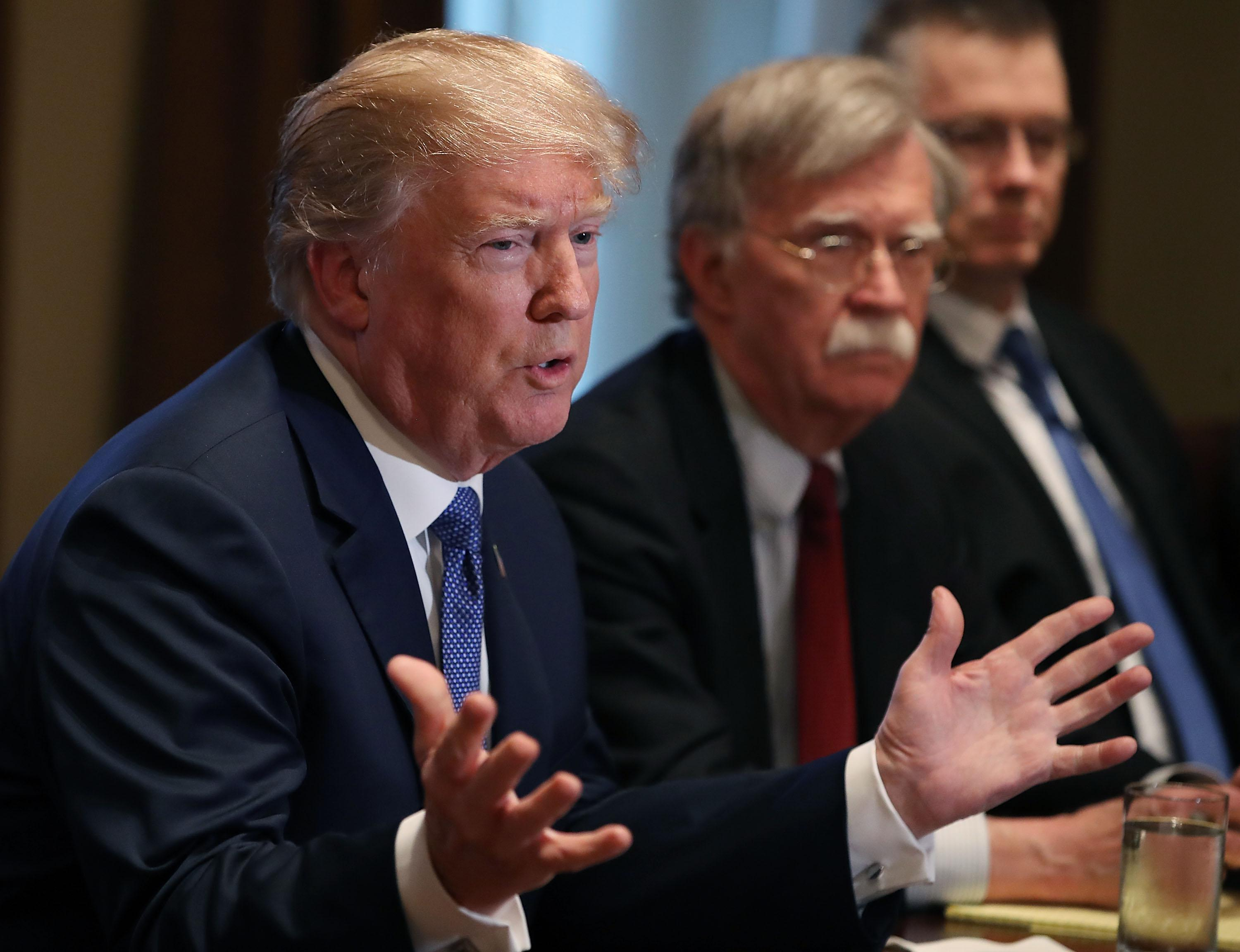WASHINGTON, DC - APRIL 09:  U.S. President Donald Trump is flanked by National Security Advisor John Bolton as he speaks about the FBI raid at his lawyer Michael Cohen's office, while receiving a briefing from senior military leaders regarding Syria,  in the Cabinet Room, on April 9, 2018 in Washington, DC. The FBI raided the office of Michael Cohen on Monday as part of the ongoing investigation into the president's administration. (Photo by Mark Wilson/Getty Images)