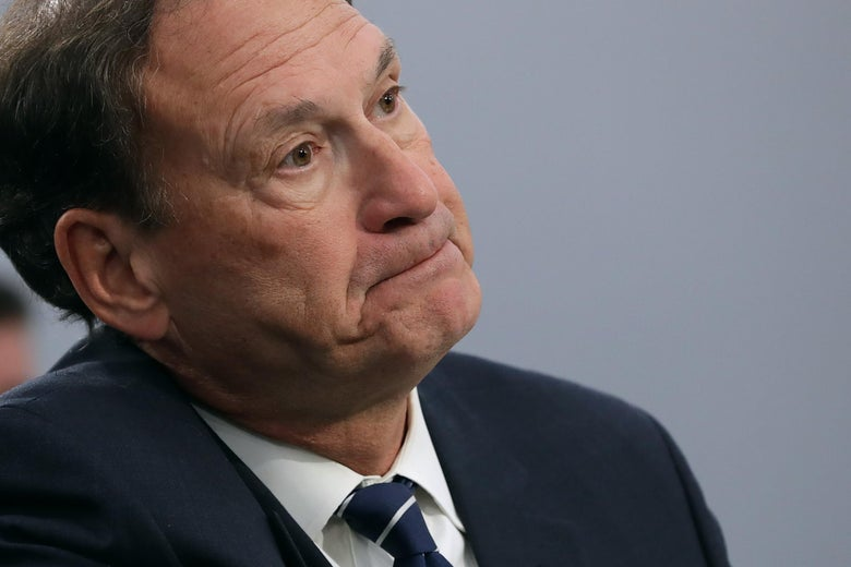 Justice Samuel Alito purses his lips and stares straight ahead.
