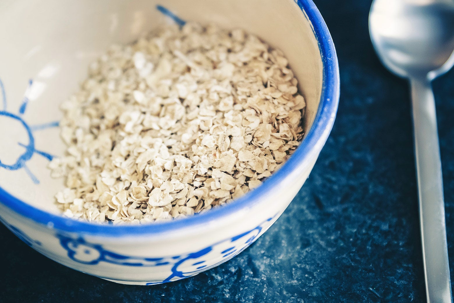 A bowl of uncooked oats beside a metal spoon.