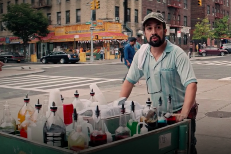 Lin Manuel Miranda, wearing an NYC cap and a cloth slung over his shoulder, pushes a cart with syrups on a New York City street.