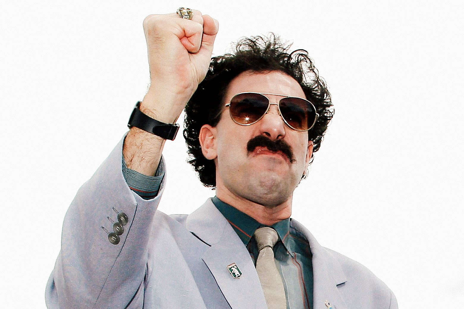 Sacha Baron Cohen, as Borat, raises his fist and scrunches up his face.