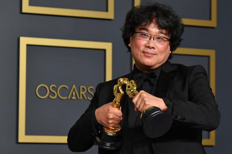 Bong Joon-ho smooshes the faces of two of his Oscars together so they kiss.
