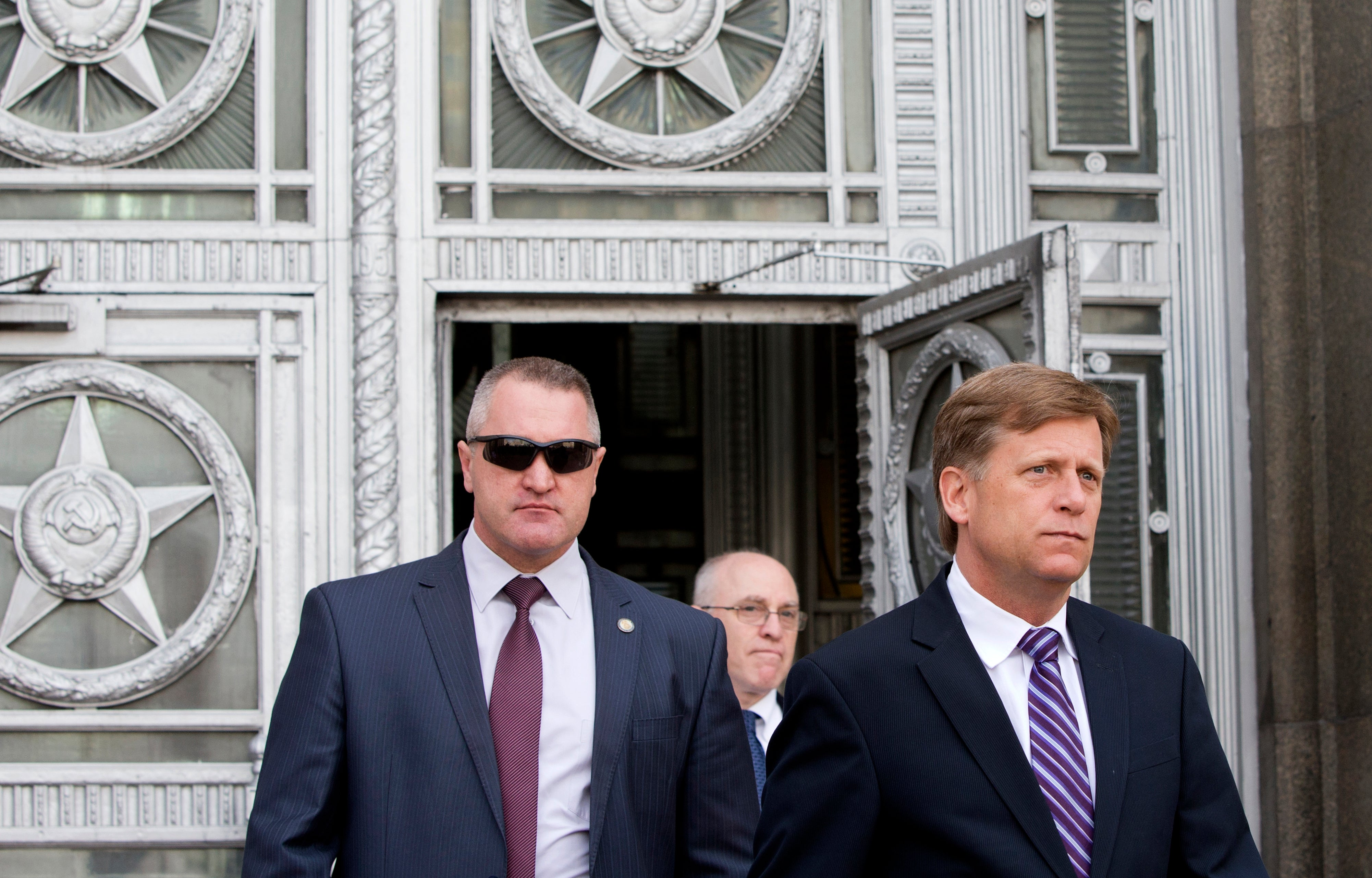 McFaul walks out of an imposing government building with an individual who appears to be a security guard by his side.
