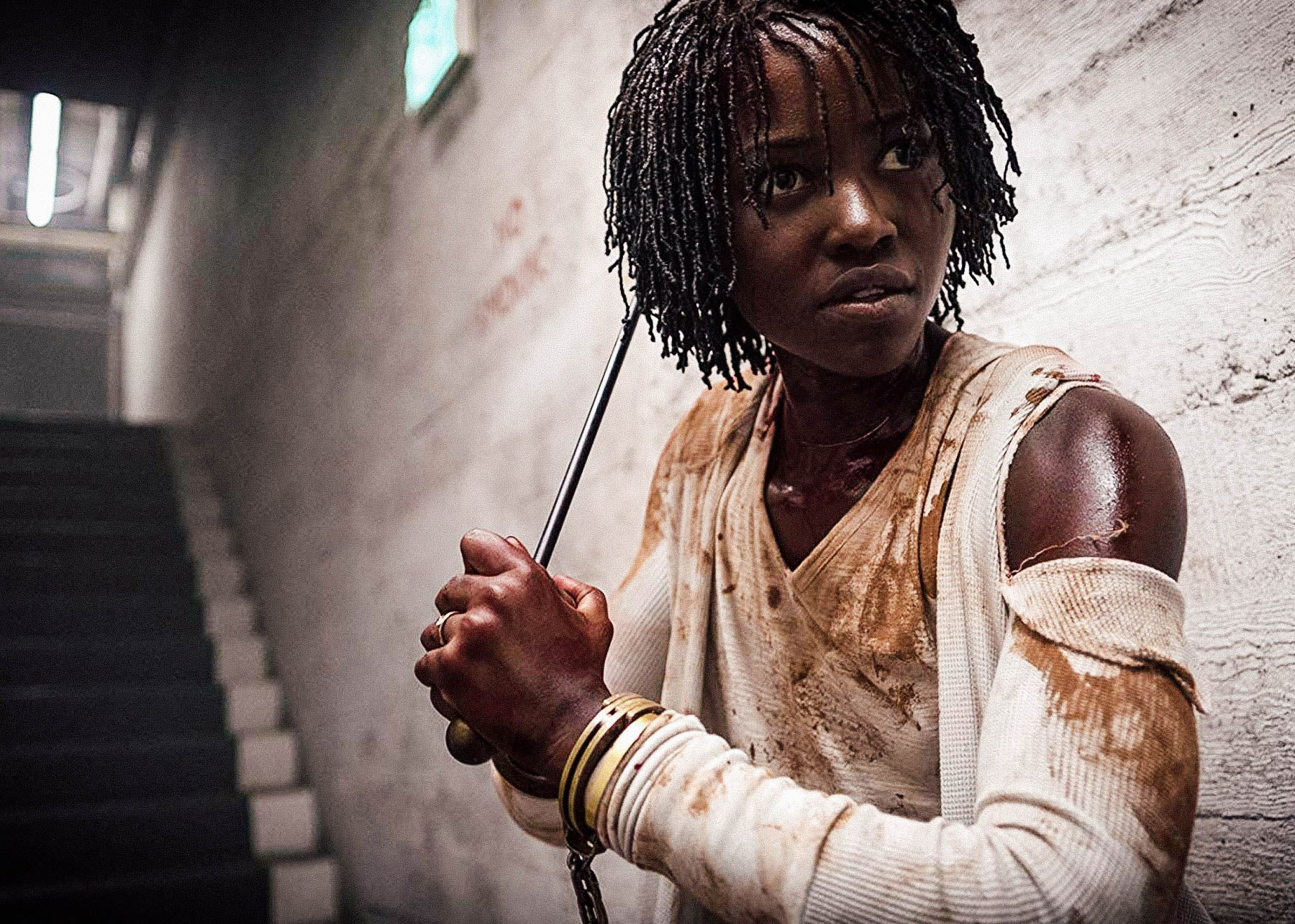 In a still from Us, Lupita Nyong'o stands at the foot of a set of stairs in a deserted hallway. She is wearing dirty clothing and brandishing a metal rod as a weapon.
