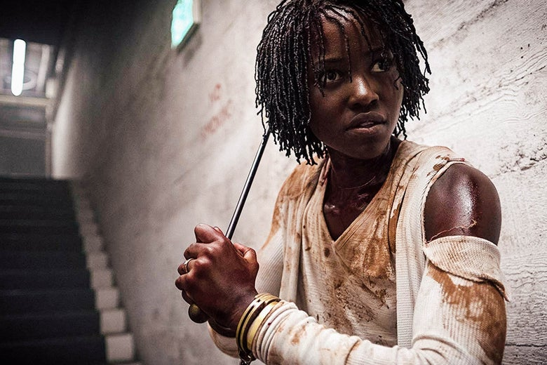 """In a still of us, Lupita Nyong'o stands at the foot of a staircase in a deserted corridor. She wears dirty clothes and brandishes a metal rod as a weapon. """"Srcset ="""" https://compote.slate.com/images/e02f09cb-5593-4235-9f5e-3f7ed24ed886.jpeg?width=780&height=520&rect=1800x1200&offset=1 0x0 1x, https://compote.slate.com/ images / e02f09cb-5593-4235-9f5e-3f7ed24ed886.jpeg? width = 780 & height = 520 & rect = 1800x1200 & offset = 0x0 2x"""