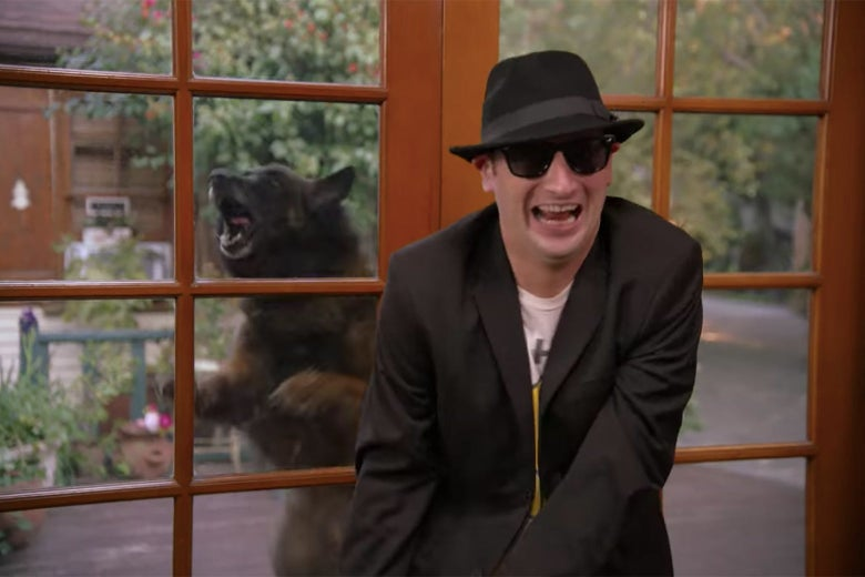 A man in a black suit and sunglasses, with a growling bear behind him.