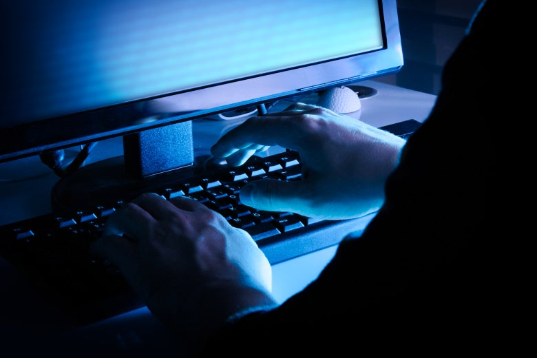 A person illicitly typing on a keyboard in a dark room.